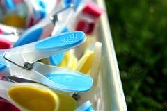 Close-up van helder gekleurde wasknijpers in een container op gras, Stock Fotografie