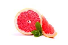 Close-up van heldere sappige grapefruit en bladeren van munt, rode citrusvrucht met een zure die pulp op een witte achtergrond wo stock afbeelding