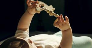 Close-up van het aanbiddelijke nieuwsgierige baby spelen met houten stuk speelgoed in het bed Weinig baby die met houten binnen s stock videobeelden