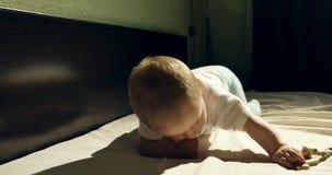 Close-up van het aanbiddelijke nieuwsgierige baby spelen met houten stuk speelgoed in het bed Weinig baby die met houten binnen s stock footage