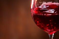 Close-up van het abstracte bespatten van de rode wijn in het breekbare wijnglas op de bruine houten achtergrond Royalty-vrije Stock Afbeeldingen