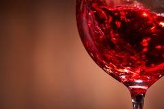 Close-up van het abstracte bespatten van de rode wijn in het breekbare wijnglas op de bruine houten achtergrond Stock Afbeelding