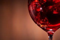 Close-up van het abstracte bespatten van de rode wijn in het breekbare wijnglas op de bruine houten achtergrond Stock Fotografie