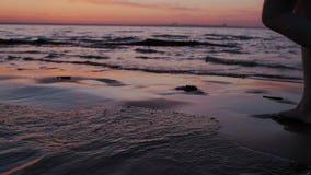 Close-up van het blootvoetse mooie vrouw lopen op oceaanzandstrand bij zonsondergang Tropische kust, vakantie Rode hemel, water stock video