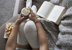 Close-up van het boek van de vrouwenlezing thuis op laag met hete chocolatemilk en koekjes stock afbeeldingen