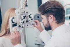 Close-up van het donkerbruine gebaarde doc.-optometrist aanpassen phoropter F royalty-vrije stock foto's
