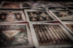 Close-up van het geheime dek van het mysticustarot en oude tarotkaarten die op lijst voor een magische heidense psychische lotsle stock foto's
