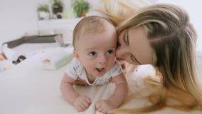 Close-up van het gelukkige jonge moeder spelen met haar jongen wordt geschoten die van de 3 maanden oudbaby op bed kruipen dat stock video