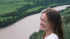 Close-up van het gezicht van een jonge vrouw tegen de achtergrond van de mooie groene vlakte stock videobeelden