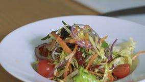 Close-up van het gieten van salade tomaat-kers op plaat langzaam stock video