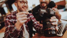 Close-up van het Glimlachen Guy Insert SD-geheugenkaart in camera stock afbeelding