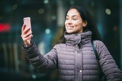 Close-up van het glimlachen het mooie bedrijfsvrouw nemen op middelbare leeftijd selfie op smartphone met vage mening op achtergr stock afbeelding