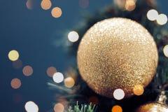 Close-up van het gouden snuisterij hangen van een verfraaide Kerstboom stock afbeelding