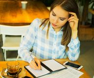 Close-up van het jonge mooie bedrijfsvrouw schrijven in notitieboekje Stock Foto