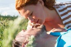 Close-up van het jonge paar openlucht romancing Sluit omhoog gezichten van aantrekkelijk paar, letten zij op elkaar in het groene Royalty-vrije Stock Afbeeldingen