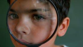 Close-up van het Kaukasische schooljongen kijken door vergrootglas tegen groene raad in klaslokaal stock footage