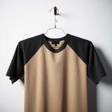 Close-up van het lege katoenen t-shirt bruine kleur hangen in centrum lege concrete muur Ontruim hoogst etiketmodel met royalty-vrije stock afbeeldingen