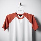 Close-up van het lege witte en oranje katoenen t-shirt hangen in centrum lege concrete muur Ontruim hoogst etiketmodel met Stock Afbeeldingen