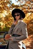 Close-up van het mooie jonge vrouw stellen dichtbij cabriolet Het seizoen van de herfst Weg in dalingsbos royalty-vrije stock afbeeldingen