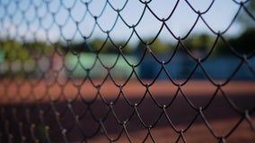 Close-up van het net die de tennisbaan insluiten De silhouetten van mensen die tennis spelen zijn zichtbaar stock videobeelden