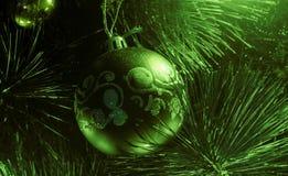 Close-up van het rode snuisterij hangen van een verfraaide Kerstboom of een abstracte nieuwe groene jaarbal met vlotte oppervlakt Stock Foto's