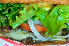 Close-up van het sappige hamburger en bevestigen Royalty-vrije Stock Afbeeldingen