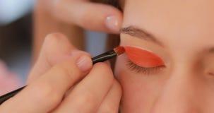 Close-up van het schilderen van oogleden in oranje kleur stock video