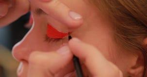 Close-up van het schilderen van oogleden in oranje kleur stock footage