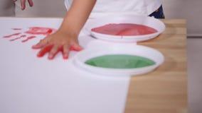 Close-up van het spel van het handmeisje het schilderen waterkleur op wit blad van document stock footage