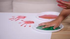 Close-up van het spel van het handmeisje het schilderen waterkleur op wit blad van document stock video