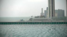 Close-up van het water in de pool op het dak tegen de achtergrond van wolkenkrabbers door de oceaan 4k, achtergrondonduidelijk be stock footage