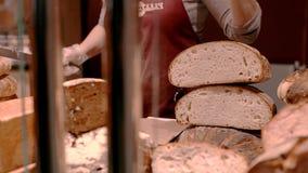 Close-up van het winkel tegen verse brood De verkoper snijdt de broodstukken stock footage
