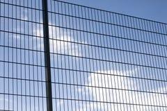Close-up van hoge abstracte geometrische beschermende donkere metaalomheining van voetbal of voetbalgebiedsspeelplaats op duideli stock foto