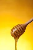 Close-up dat van houten dipper en stromende honing wordt geschoten stock foto's