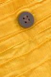 Close-up van houten knoop op geel organisch katoen Royalty-vrije Stock Fotografie