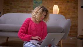 Close-up van huisvrouw in roze sweater wordt geschoten die aandachtig in laptop met grote concentratie in huisatmosfeer die surfe stock video