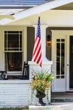 Close-up van ingang aan plattelandshuisjehuis met mooie bloemen in een pot en een Amerikaanse vlag door portiek royalty-vrije stock foto