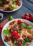 Close-up van Italiaanse spaghetti met tomatensaus, Parmezaanse kaaskaas en vers basilicum op bovenkant, op donkere achtergrond royalty-vrije stock afbeelding