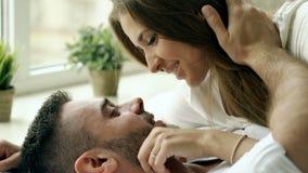 Close-up van jong mooi en het houden van paarspel en kus in bed bij de ochtend Aantrekkelijke mens die en van hem kussen koestere stock footage