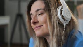 Close-up van jong mooi meisje die in blauwe uitrusting van de muziek thuis genieten Vrouw het luisteren muziek in hoofdtelefoons  stock videobeelden