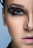 Close-up van jong vrouwengezicht wordt geschoten met futuristische make-up die Stock Foto