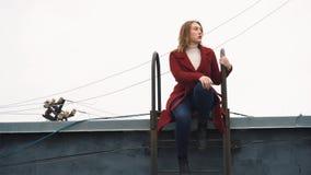 Close-up van jonge aantrekkelijke vrouw die in rode laag, witte col en jeans op de treden van een dak zitten media foto royalty-vrije stock afbeelding
