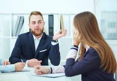 Close-up van jonge bedrijfsmensen die bij conferentielijst zitten communicating stock afbeelding