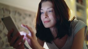 Close-up van jonge glimlachende vrouw die smartphone gebruiken die in bed thuis bij nacht liggen stock videobeelden