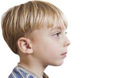 Close-up van jonge jongen die exemplaarruimte bekijken over witte achtergrond Stock Foto