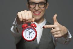 Close-up van jonge onderneemster of beambte die rode klok in handen houden royalty-vrije stock afbeeldingen