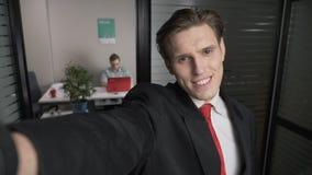 Close-up van jonge succesvolle zakenman die in kostuum voor Selfies glimlachen De mensenwerken aangaande een computer op de achte stock videobeelden
