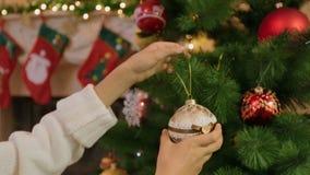 Close-up van jonge vrouw wordt geschoten die Kerstboom met snuisterijen verfraaien die stock videobeelden
