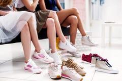 Close-up van jonge vrouwen wordt geschoten die op verschillend schoeisel proberen terwijl het zitten in een schoenopslag die royalty-vrije stock foto's
