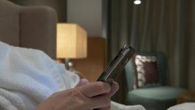 Close-up van jonge vrouwenhanden die sms het scrollen telefoonbeelden typen de vrouwelijke handen gebruiken een smartphone in de  stock video